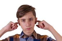 Adolescente serio en la camisa de tela escocesa que sostiene los fingeres en oídos Imagen de archivo