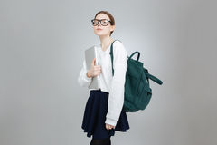Adolescente serio en vidrios con la mochila que sostiene el ordenador portátil Foto de archivo libre de regalías