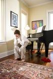 Adolescente serio que se sienta en banco del piano Imagen de archivo