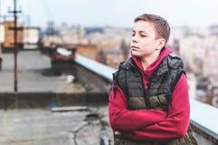 Adolescente serio que se sienta en el tejado de la casa Imagen de archivo libre de regalías