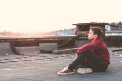 Adolescente serio que se sienta en el tejado de la casa Fotos de archivo libres de regalías