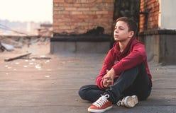 Adolescente serio que se sienta en el tejado de la casa Fotografía de archivo