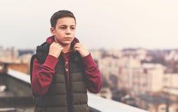 Adolescente serio que se sienta en el tejado de la casa Fotografía de archivo libre de regalías