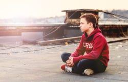 Adolescente serio que se sienta en el tejado de la casa Imagenes de archivo