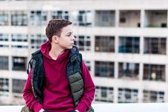 Adolescente serio que se sienta en el tejado de la casa Fotos de archivo