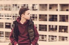 Adolescente serio que se sienta en el tejado de la casa Foto de archivo libre de regalías