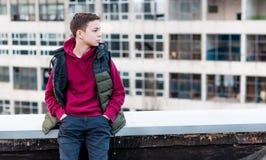 Adolescente serio que se sienta en el tejado de la casa Imágenes de archivo libres de regalías