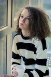 Adolescente serio que se sienta por la ventana Foto de archivo libre de regalías