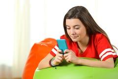 Adolescente serio usando un teléfono elegante en un taburete Imagen de archivo