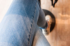 Adolescente siéntese con sus piernas cruzadas Imagen de archivo
