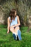 Adolescente siéntese en hierba Fotografía de archivo libre de regalías