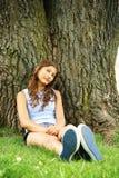 Adolescente siéntese en un árbol Imagen de archivo libre de regalías