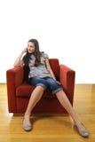 Adolescente siéntese en un sofá Fotos de archivo