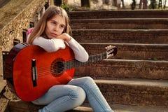 Adolescente soñador que sostiene una guitarra en su revestimiento y que mira lejos Fotos de archivo libres de regalías