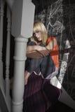 Adolescente solo que abraza rodillas en pasos en casa Foto de archivo libre de regalías