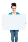 Adolescente sonriente adorable que lleva a cabo la tarjeta grande del anuncio Imágenes de archivo libres de regalías