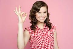 Adolescente sonriente atractivo que muestra la muestra aceptable Imagen de archivo libre de regalías