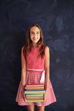 Adolescente sonriente bonito que sostiene una pila de libros contra scho Imagenes de archivo