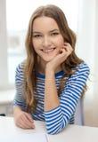 Adolescente sonriente con el cuaderno en casa Foto de archivo libre de regalías