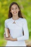 Adolescente sonriente con el libro rojo Fotos de archivo libres de regalías
