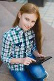 Adolescente sonriente con el ordenador de la PC de la tableta al aire libre Fotos de archivo libres de regalías