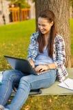 Adolescente sonriente con el ordenador portátil Imágenes de archivo libres de regalías