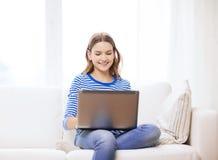 Adolescente sonriente con el ordenador portátil en casa Imagen de archivo libre de regalías