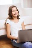 Adolescente sonriente con el ordenador portátil en casa Imágenes de archivo libres de regalías