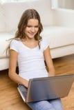 Adolescente sonriente con el ordenador portátil en casa Imagen de archivo