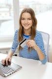 Adolescente sonriente con el ordenador portátil en casa Imagenes de archivo