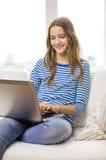 Adolescente sonriente con el ordenador portátil en casa Fotos de archivo libres de regalías