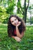 Adolescente sonriente con el pelo rizado que miente en una hierba verde Imágenes de archivo libres de regalías