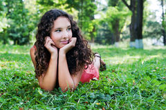 Adolescente sonriente con el pelo rizado que miente en una hierba verde Imagen de archivo libre de regalías
