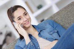 Adolescente sonriente con el smartphone que se sienta en el sofá en casa Imagen de archivo
