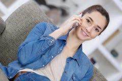 Adolescente sonriente con el smartphone que se sienta en el sofá en casa Foto de archivo