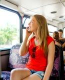 Adolescente sonriente con el smartphone que va en autobús Imagenes de archivo