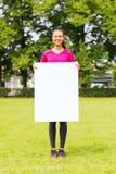 Adolescente sonriente con el tablero blanco en blanco Fotografía de archivo libre de regalías