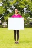 Adolescente sonriente con el tablero blanco en blanco Imagenes de archivo