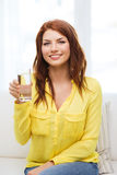 Adolescente sonriente con el vidrio de agua en casa Fotos de archivo