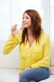 Adolescente sonriente con el vidrio de agua en casa Fotografía de archivo libre de regalías