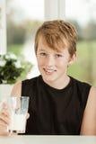 Adolescente sonriente con el vidrio de leche Imagenes de archivo