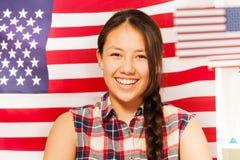 Adolescente sonriente con la bandera americana detrás de ella Imagenes de archivo