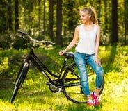 Adolescente sonriente con la bicicleta en un parque Imagenes de archivo