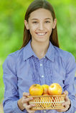 Adolescente sonriente con la cesta de manzanas Imagen de archivo