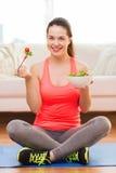 Adolescente sonriente con la ensalada verde en casa Imagen de archivo