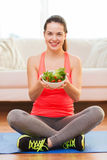 Adolescente sonriente con la ensalada verde en casa Imagen de archivo libre de regalías