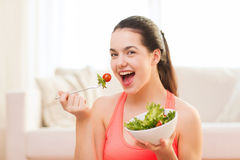 Adolescente sonriente con la ensalada verde en casa Fotografía de archivo libre de regalías