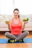 Adolescente sonriente con la ensalada verde y la hamburguesa Fotografía de archivo
