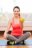 Adolescente sonriente con la manzana verde en casa Imagenes de archivo