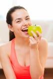 Adolescente sonriente con la manzana verde en casa Imagen de archivo libre de regalías
